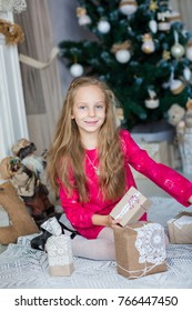Happy little girl near Xmas tree with presents near fireplace