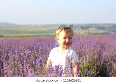 Happy little girl on a lavender background. Cute baby playing in meadow field. Family holiday in summer day.