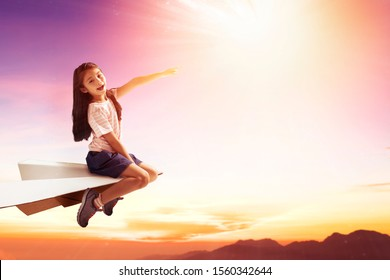 happy little  girl on paper plane and  flying in the sky