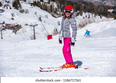 Happy little girl on the ski slopes playing with snow