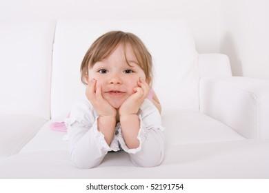 happy little girl on white sofa