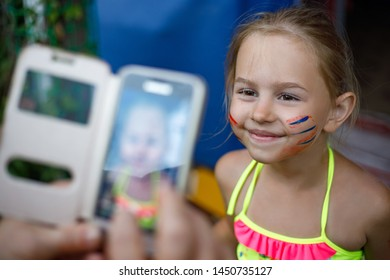 Happy little girl with painted face posing while being photographed on smartphone