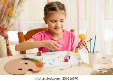 Happy little girl painting eggs for Easter