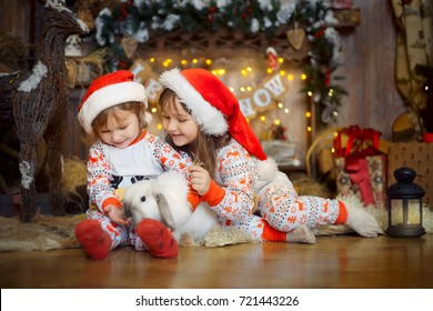 Happy little girl in pajamas playing with bunny near a fireplace at Christmas Eve