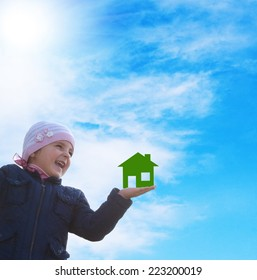 Happy little girl with paper green home on hand  on a sky blue background