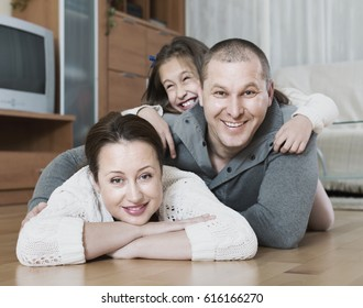 Happy little girl with parents posing at floor and smiling. Focus on woman