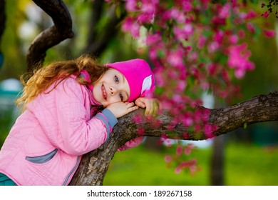 happy little girl in the park climbed on tree
