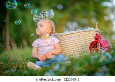 happy little girl in the park at the river, sits on a grass, start up soap puzir, laugh and smile