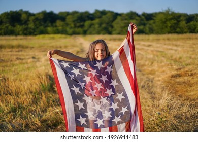 Happy little girl patriot running in the field with American flag. USA celebrate 4th of July