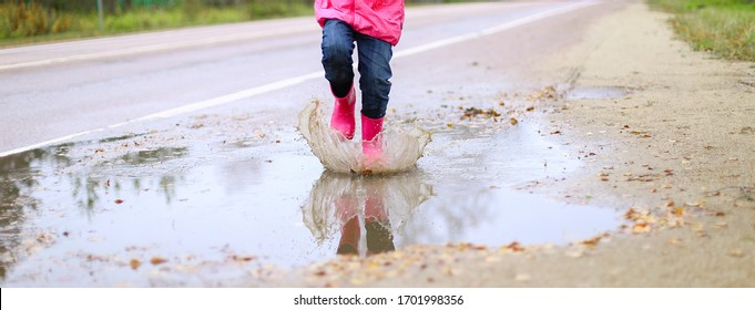 Happy little girl in pink waterproof jacket, rubber boots cheerfully jumps through puddles on street road in rainy weather. Spring, autumn. Children's fun in fresh air after rain. Outdoors recreation.