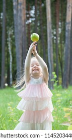 Happy little girl playing with apple in a summer park