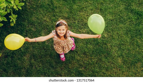 Happy little girl playing with colorful balloons outdoors, top view