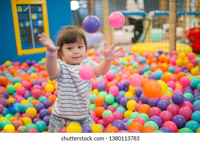 Happy little girl playing in colorful plastic balls.