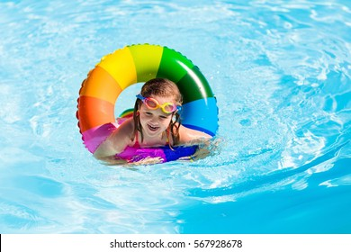 Happy little girl playing with colorful inflatable ring in outdoor swimming pool on hot summer day. Kids learn to swim. Children wearing sun protection rash guard relaxing in tropical resort.