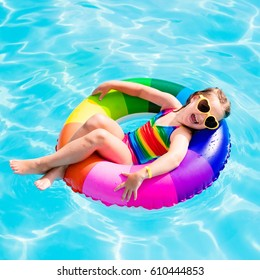 Happy little girl playing with colorful inflatable ring in outdoor swimming pool on hot summer day. Kids learn to swim. Child water toys. Children play in tropical resort. Family beach vacation