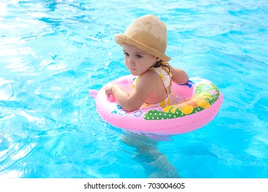 Happy little girl playing with colorful inflatable ring in the outdoor pool on a hot summer day. Children learn to swim. Children's water games.Family beach vacation.