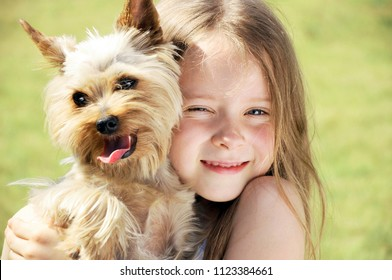 Happy little girl is playing with a dog