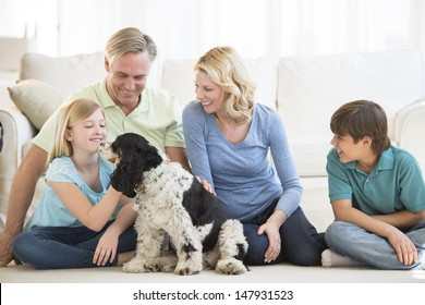 Happy little girl playing with dog while family looking at her in living room