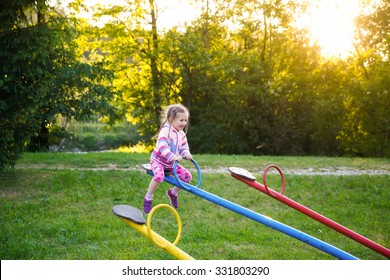 Happy little girl playing, going up ad down on a seesaw on a grassy playground in unspoiled nature among trees. Healthy childhood concept.
