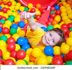 Happy little girl playing and having fun at kindergarten with colorful balls and show thumb up in play center