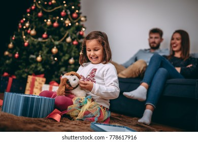 Happy little girl playing with her Christmas present stuffed puppy toy while sitting at home with her parents in front of the Christmas tree.