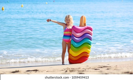 Happy little girl playing with inflatable mattess in the sea or ocean. Child having fun on sandy beach. Cute kid enjoy vacation in hotel or resort. Luxury summer destination for family with children.