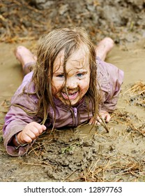 Happy Little Girl Playing in the Mud