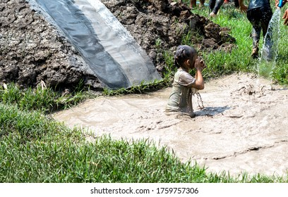 Happy Little girl playing in a mud puddle