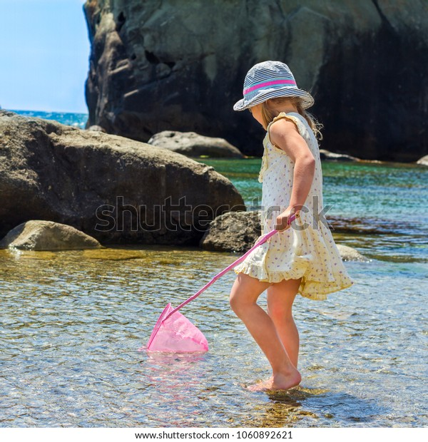 Happy little girl playing with net on the ocean beach