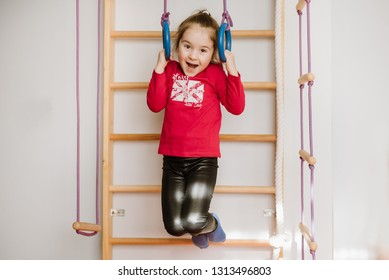Happy little girl playing on the monkey bars and have fun at home