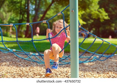 Happy little girl playing at playground in summer day