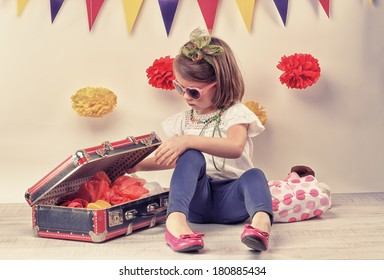 happy little girl playing with a little retro suitcase and vintage camera