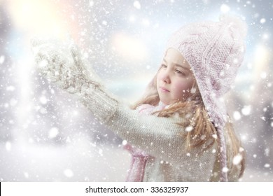 Happy little girl playing with snow.