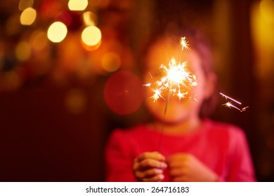 A happy little girl playing with a sparkler