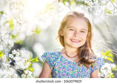 Happy little girl playing in spring cherry garden