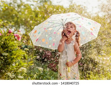 Happy little girl plays in garden under the summer rain with an umbrella. Expressive facial emotion.