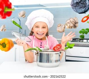 happy little girl preparing vegetarian soup in the kitchen
