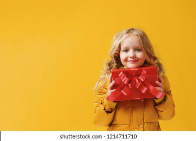 Happy little girl preschooler in a winter jacket is holding a box with a gift. The concept of giving and receiving gifts. Yellow on a yellow background, red.