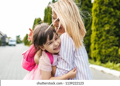 Happy little girl and pretty mother embracing each other on sidewalk next to the trees. Mom play together with kid preschooler with backpack outdoor. Mom and child have fun. Mother's day concept.