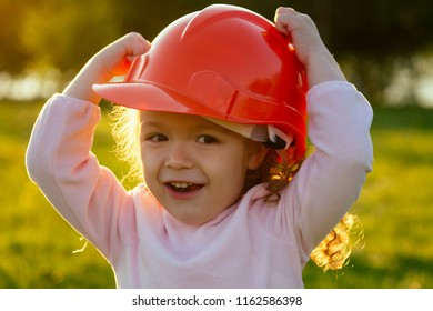 happy and little girl putting on a helmet hard hat in summer park, career guidance idea