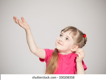 Happy little girl reaching out her palm and catching something, neutral background