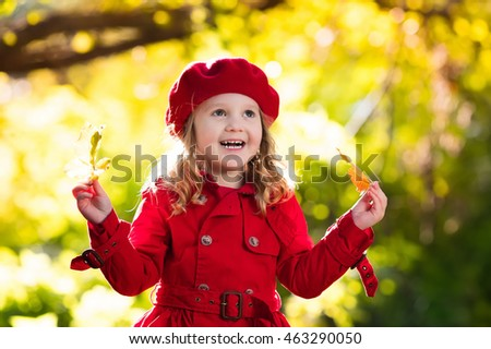 Happy little girl in red beret and trench coat playing in beautiful autumn  park on warm fcae593a2de