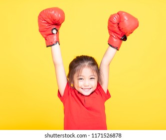 happy little girl with red boxing gloves on yellow background