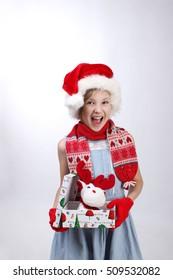 Happy little girl in red Santa helper hat holding Christmas present over light background