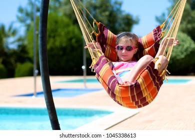 Happy little girl relaxing in hammock next to swimming pool. Cute kid enjoying summer vacation in beautiful villa or resort. Luxury summer vacation for family with children.
