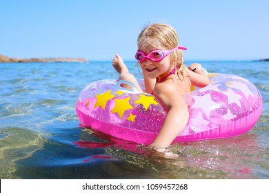 Happy little girl relaxing in inflatable ring in the sea or ocean. Cute kid enjoying summer vacation in beautiful resort. Luxury summer destination for family with children. Child learning to swim.