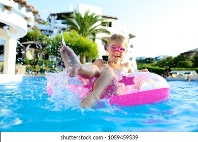Happy little girl relaxing in inflatable ring in the open air swimming pool. Cute kid enjoying summer vacation in beautiful resort or private villa. Luxury summer destination for family with children.