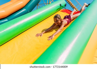 Happy little girl rides on the water slide of the water Park. Summer Sunny day