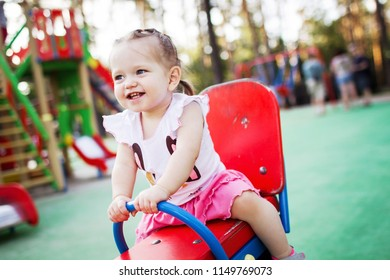 Happy little girl is riding on a swing.