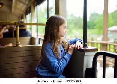 Happy little girl riding a train in a theme park or funfair on summer vacations